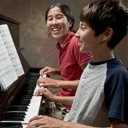 Two kids playing the piano